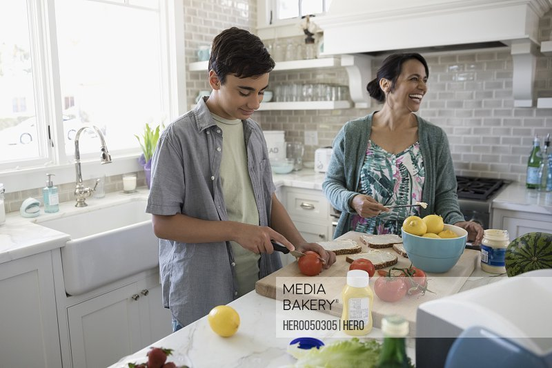 Mother and son making sandwiches in kitchen