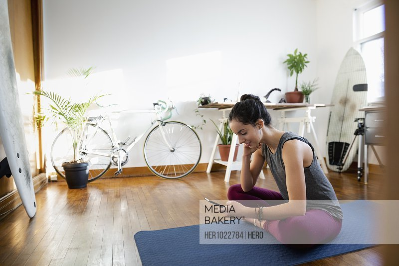 Young Latinx woman with smart phone on yoga mat in apartment