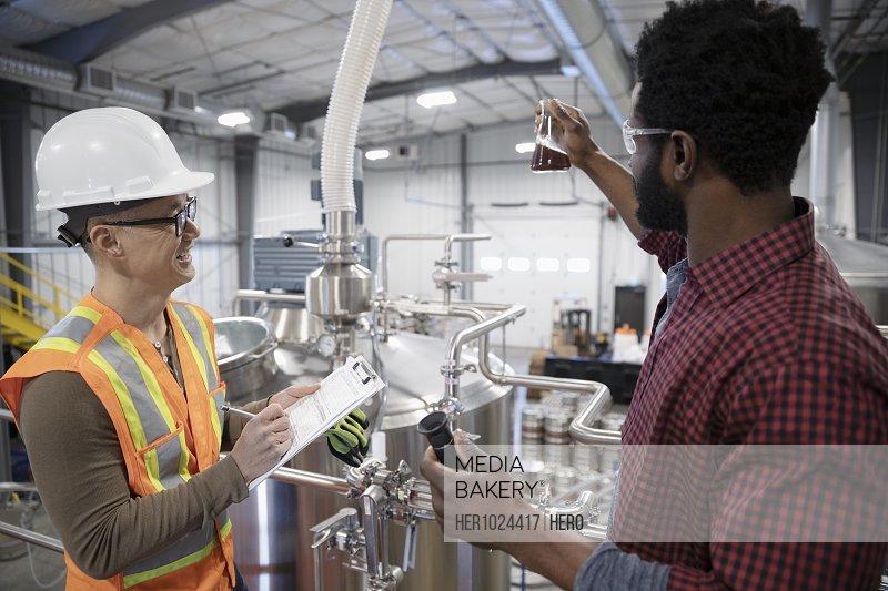 Brewers examining beer in brewhouse distillery