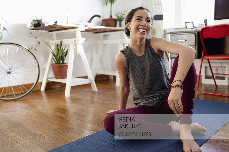 Happy young Latinx woman practicing yoga at home