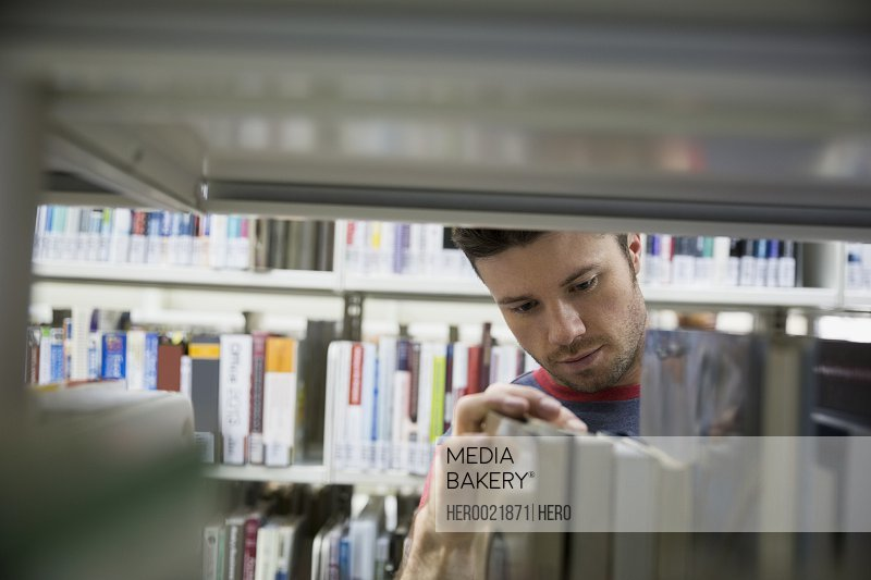 College student selecting book from library bookshelf