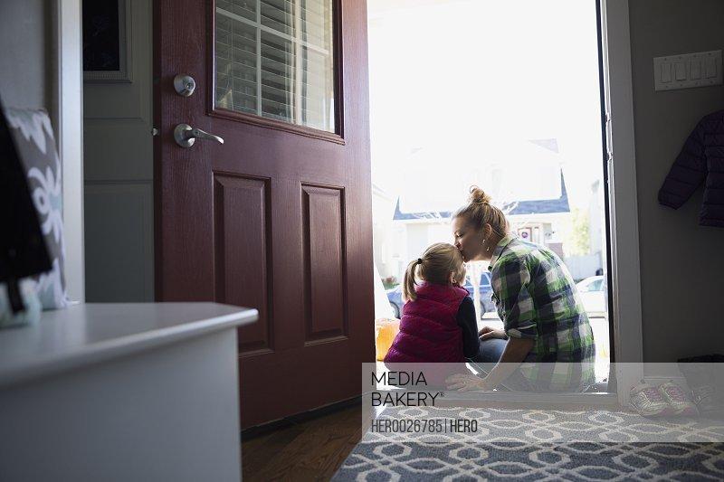 Mother kissing daughter forehead in doorway