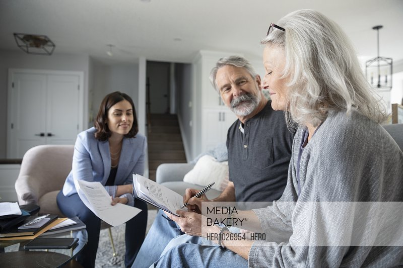 Financial advisor watching senior couple signing contract in living room