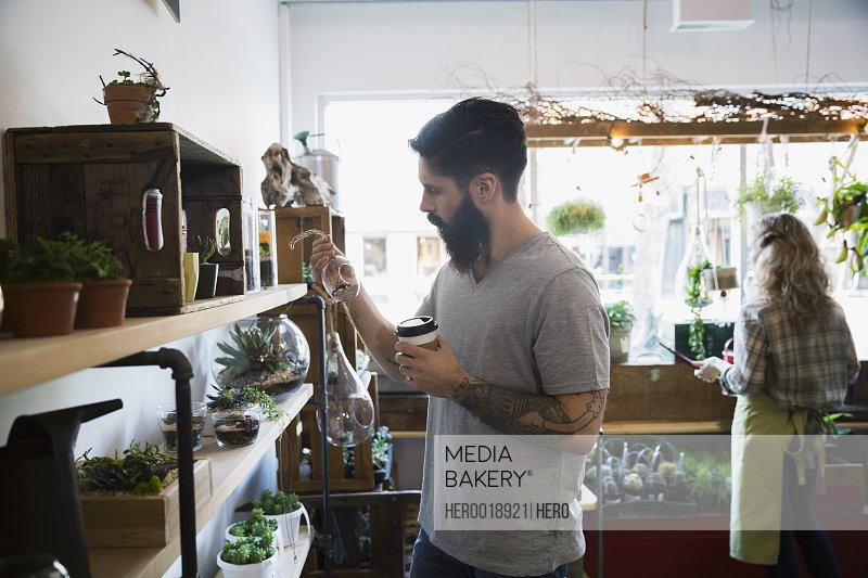 Man with coffee browsing in terrarium shop
