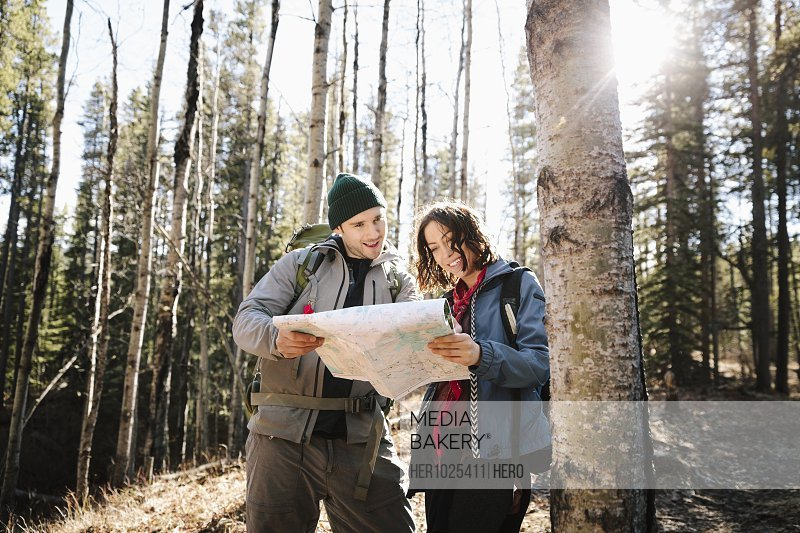 Couple with map hiking in sunny woods