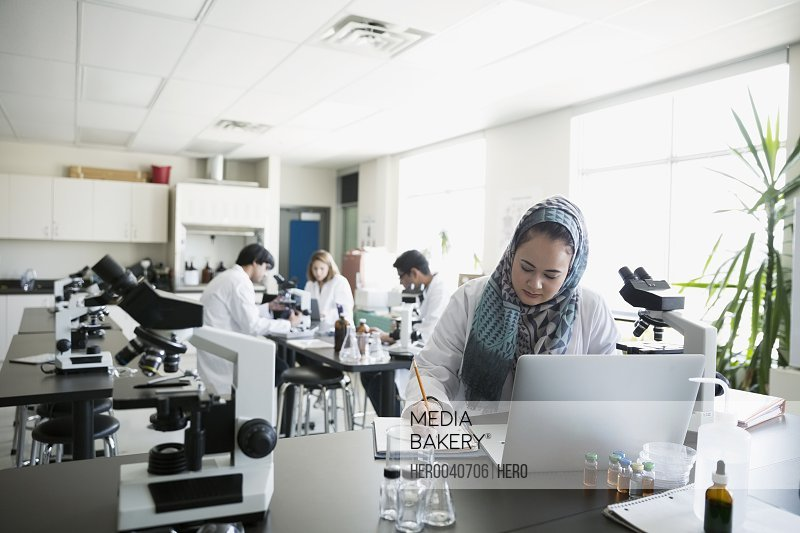 College student wearing hijab at laptop in science laboratory
