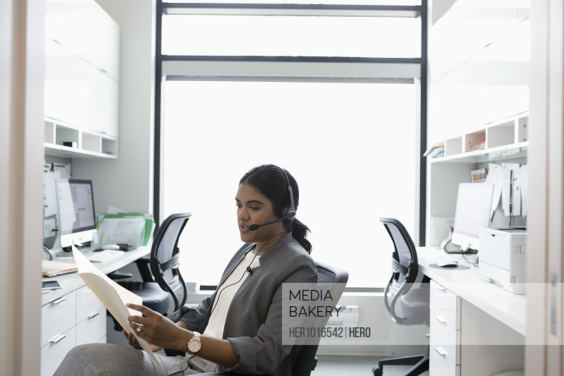 Female doctor with hands-free telephone reviewing medical record in clinic office