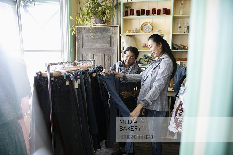Women shopping for jeans in vintage clothing shop