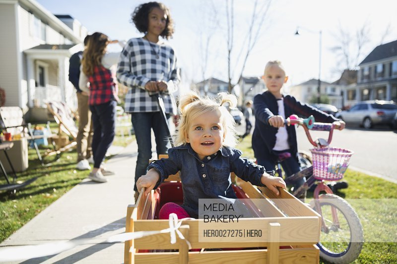 Cute girl riding in wagon on neighborhood sidewalk