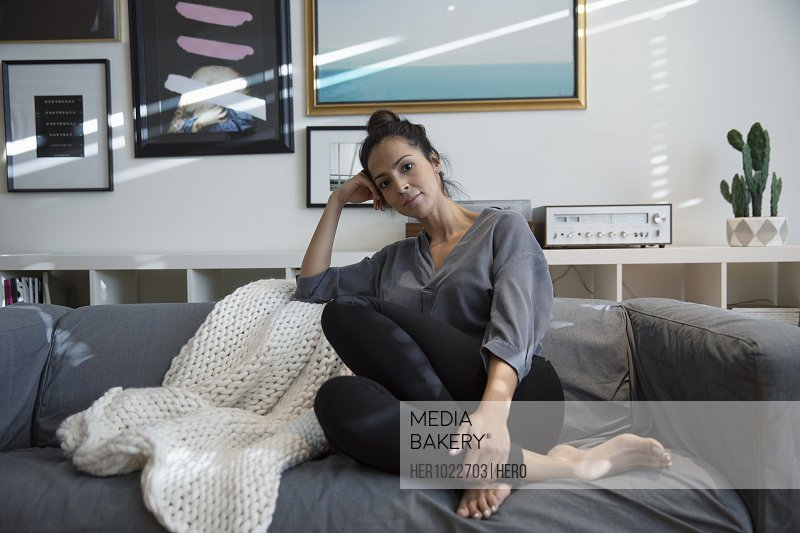Portrait confident Latina woman relaxing on living room sofa