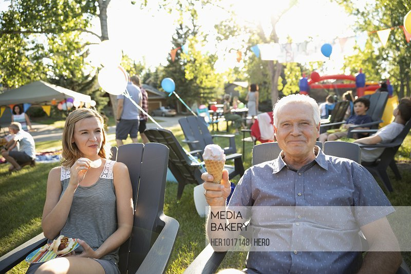 Portrait carefree senior man eating ice cream cone with daughter at summer neighborhood block party in park