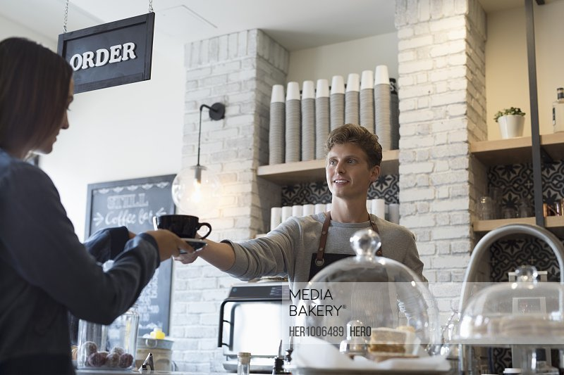 Male barista serving coffee to female customer in cafe