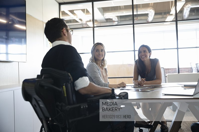 Businessman in wheelchair talking to female colleagues