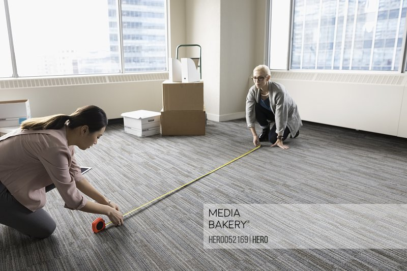 Businesswomen with tape measure measuring floor space in new office