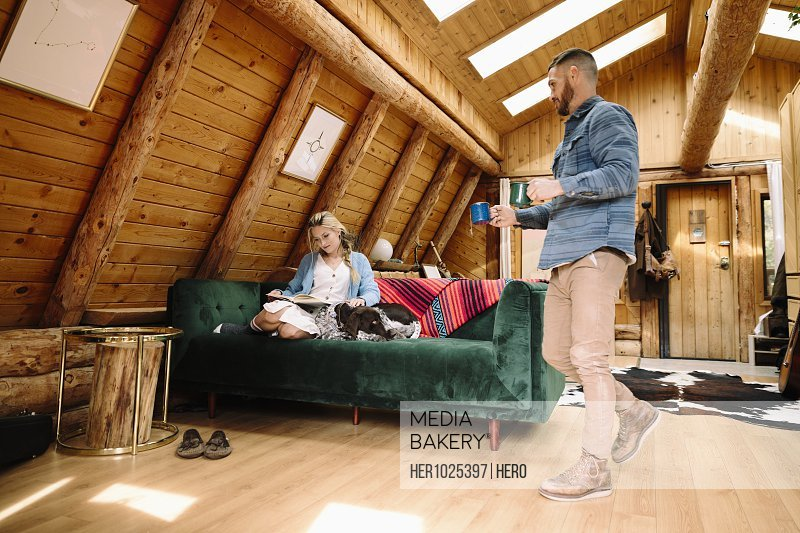 Husband serving coffee to wife reading and relaxing on cabin sofa with dog