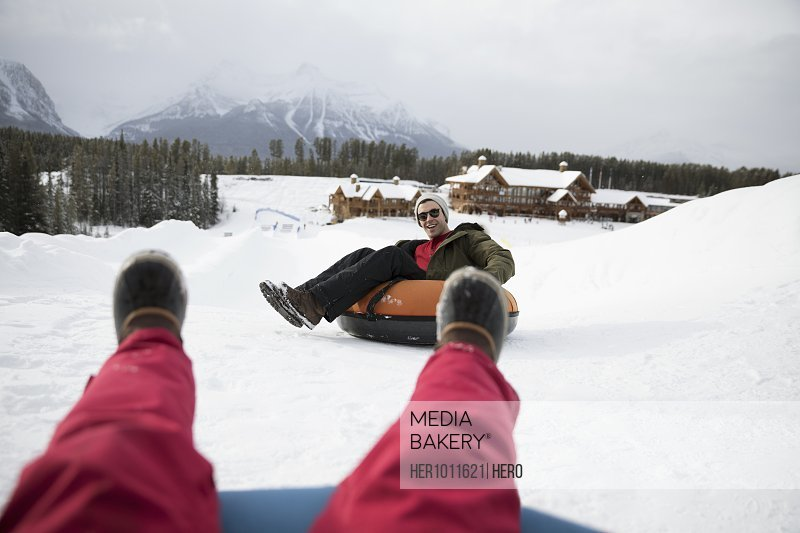 Personal perspective friends riding inner tubes in snow outside ski resort