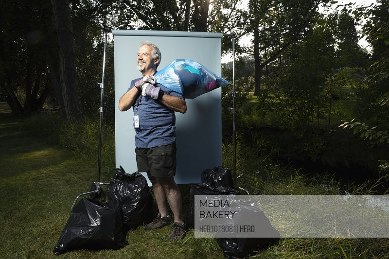 Confident senior man volunteering, cleaning up garbage in park, posing against white screen