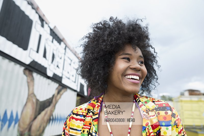 Portrait enthusiastic young woman with curly black afro looking away