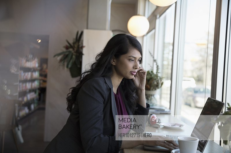 Focused businesswoman working at laptop in cafe