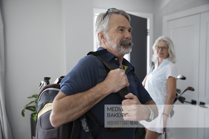 Smiling senior couple with golf bags leaving home