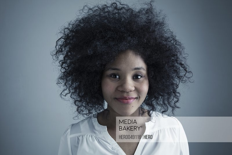 Portrait confident mixed race young woman with curly black afro hair