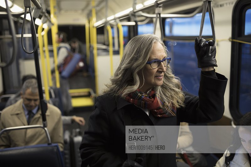 Thoughtful mature businesswoman commuter riding bus