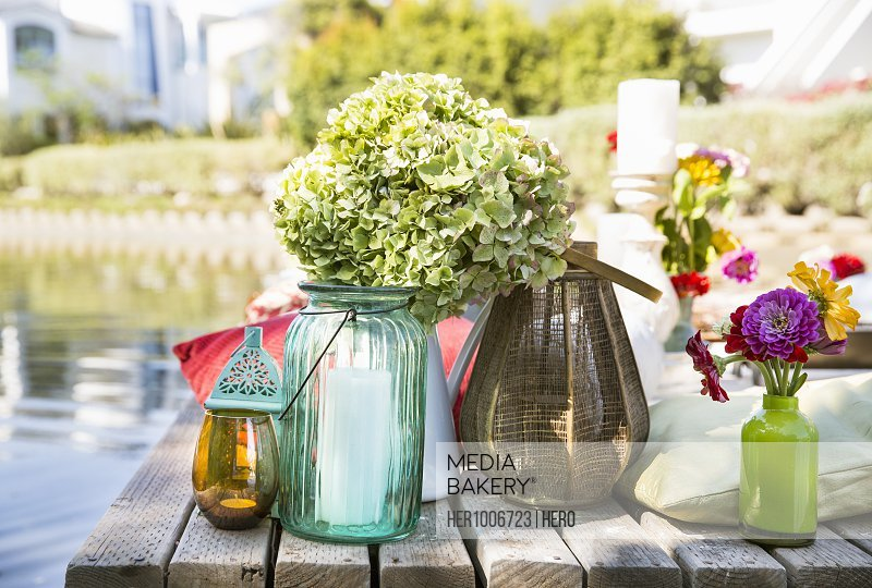 Green hydrangeas, summer flowers and candles on summer dock at lakeside