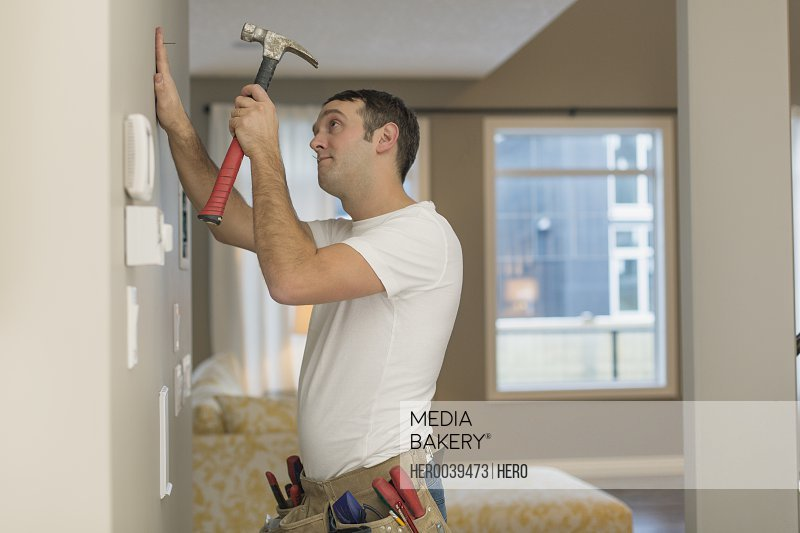 Mid adult man about to hammer nail into wall