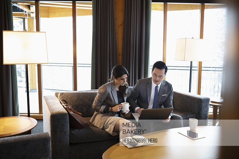 Business people meeting, drinking coffee and using laptop in hotel lobby