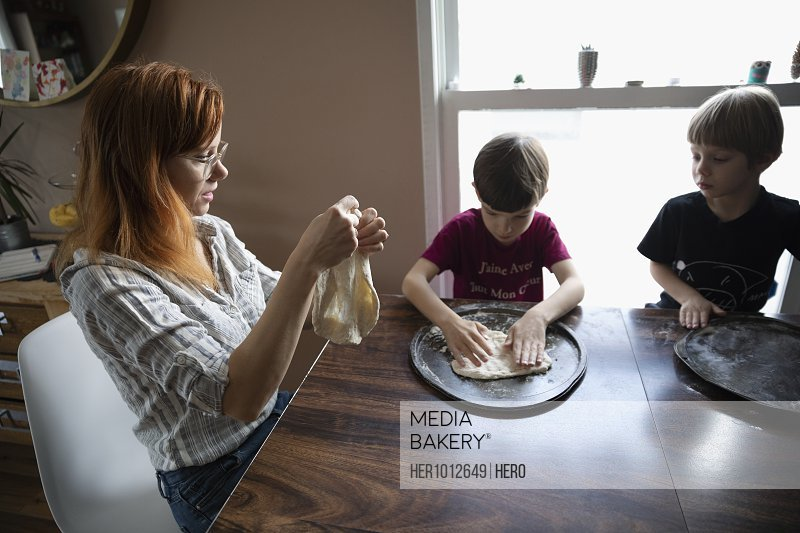 Mother and sons making homemade pizza dough at dining table