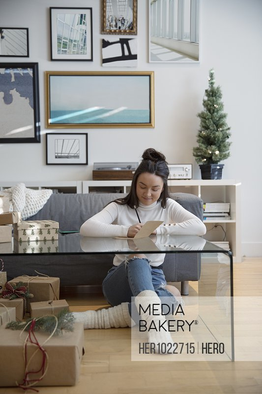 Young woman wrapping Christmas gifts and writing in card in living room