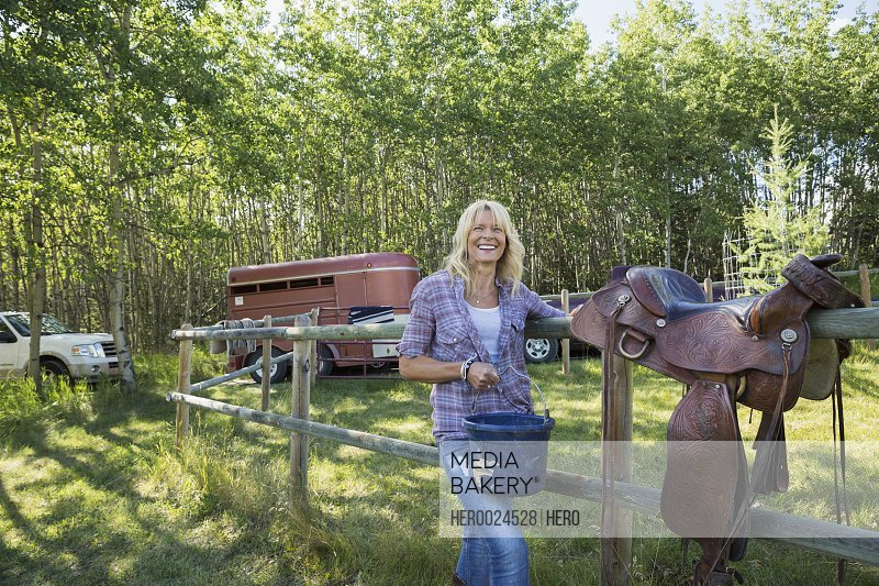 Portrait smiling woman with saddle and pail pasture