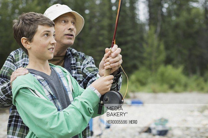 Grandfather teaching grandson to fish