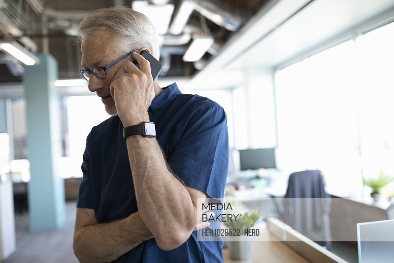 Portrait of senior business owner on cell phone in office