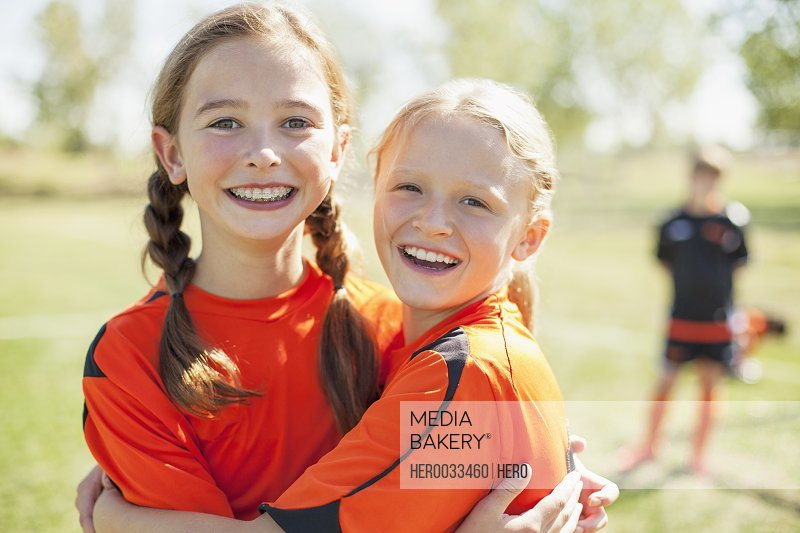 Girl soccer players smiling and hugging