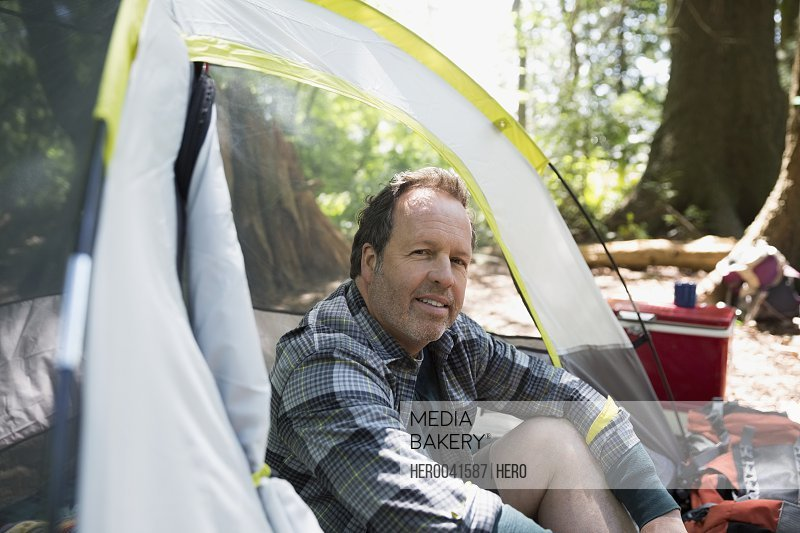 Portrait smiling man sitting inside camping tent