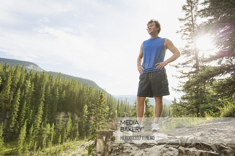 male runner pausing on rock cliff in woods