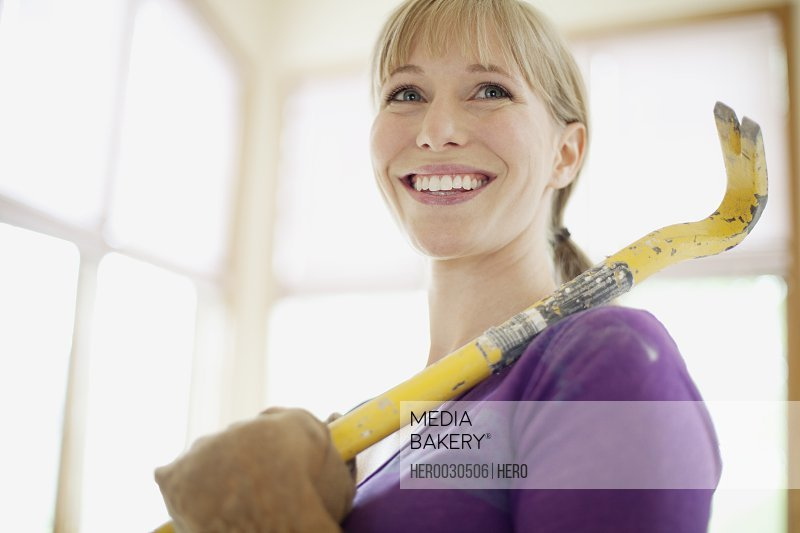 mid adult woman with crowbar for demolition