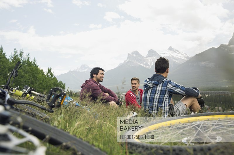 Men with mountain bikes sitting in grass