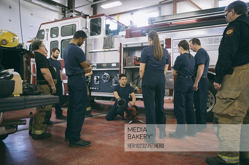 Firefighters meeting, checking equipment at fire engine at fire station