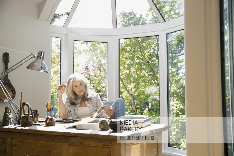 Senior woman reading book in home office