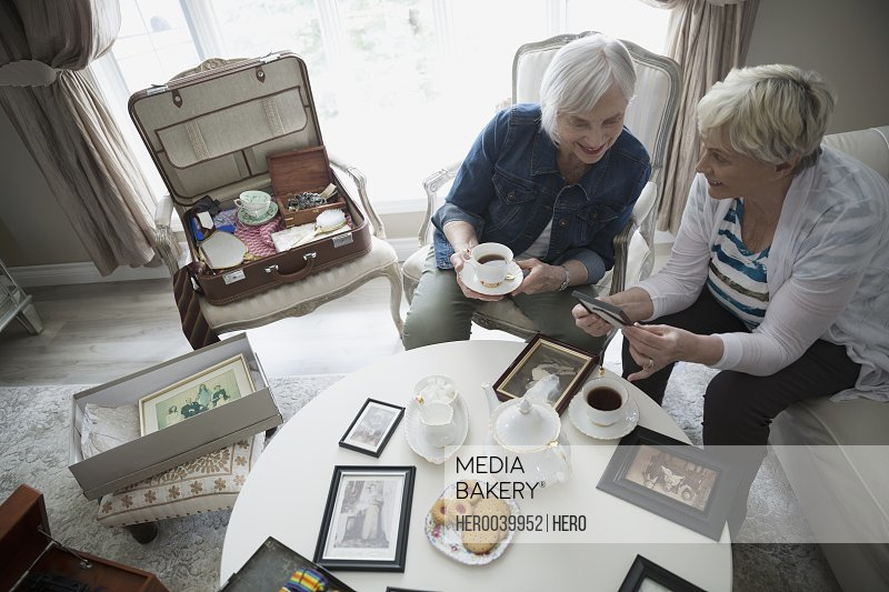 Senior women drinking tea and looking at old photographs