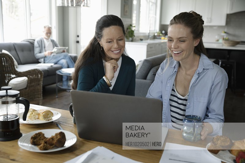 Mother and adult daughter using laptop at dining table