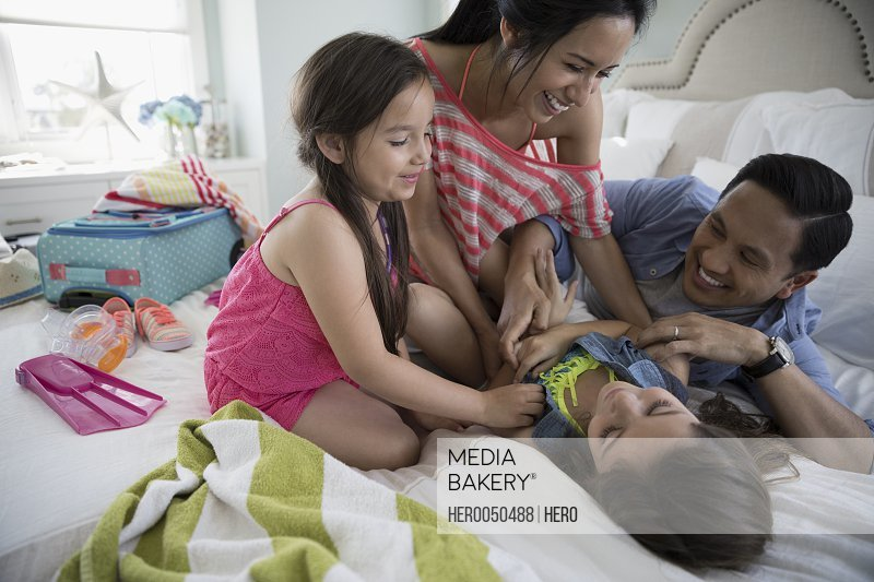 Playful family tickling packing for vacation on bed