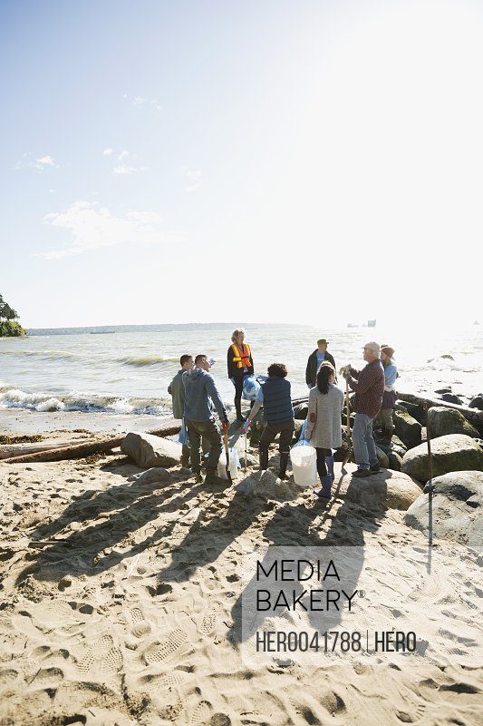 Woman leading beach cleanup volunteers on sunny beach rocks
