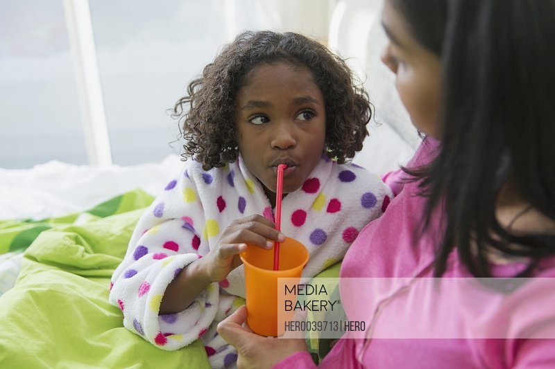 Mother giving daughter a drink in bed