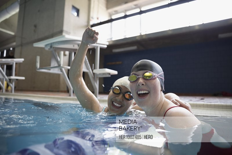 Portrait smiling female swimmers cheering and celebrating in swimming pool