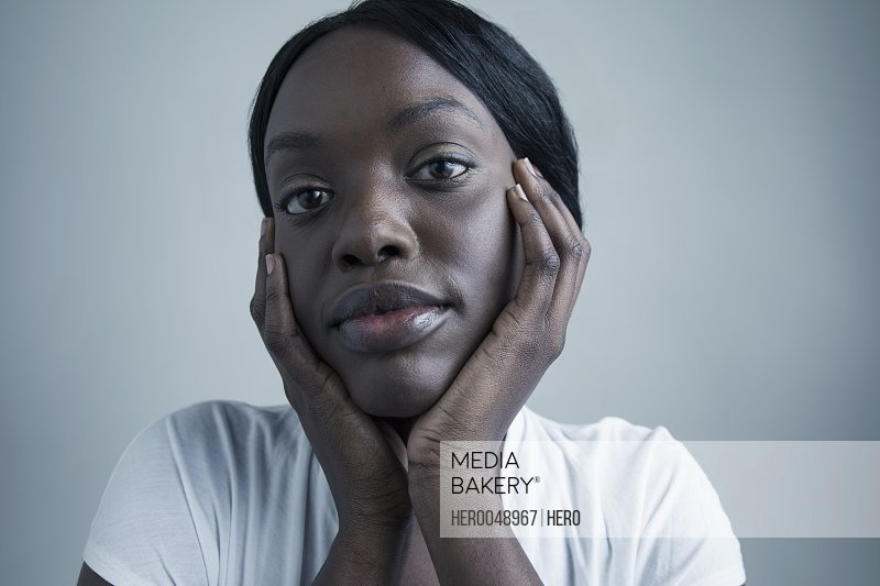 Close up portrait serious African American young woman with head in hands