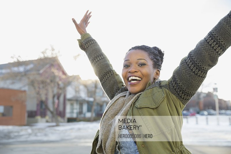 Excited woman with arms raised outdoors