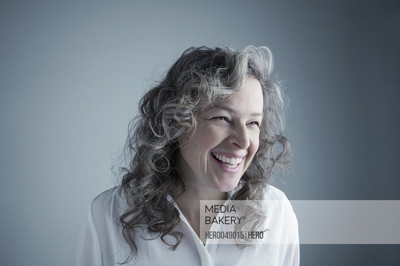 Portrait laughing Caucasian mature woman with curly gray hair